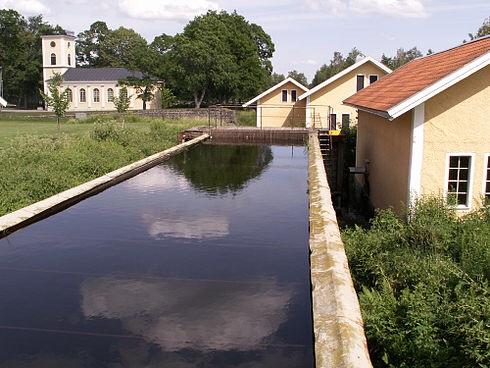 Kraftverket med tillhörande kraftverksdamm, i bakgrunden Brevens bruks kyrka. Foto från svenska Wikipedia. Uppgift om fotograf saknas.